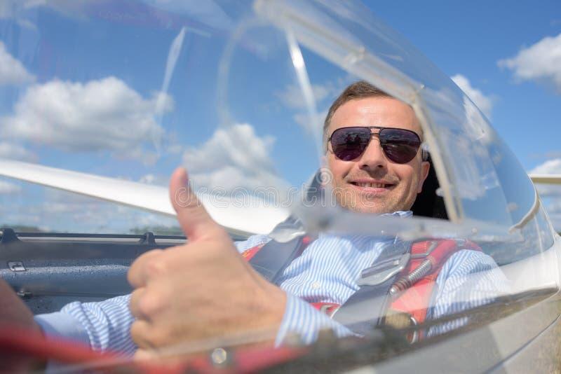 Szybowcowy pilot uśmiecha się aprobaty i pokazuje fotografia stock