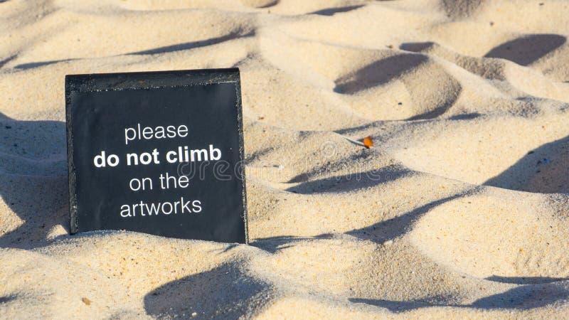 Szyldowy «Zadawalam no wspina się na grafika czarnego kwadrata znaku ostrzegawczym na piasek powierzchni zdjęcie royalty free