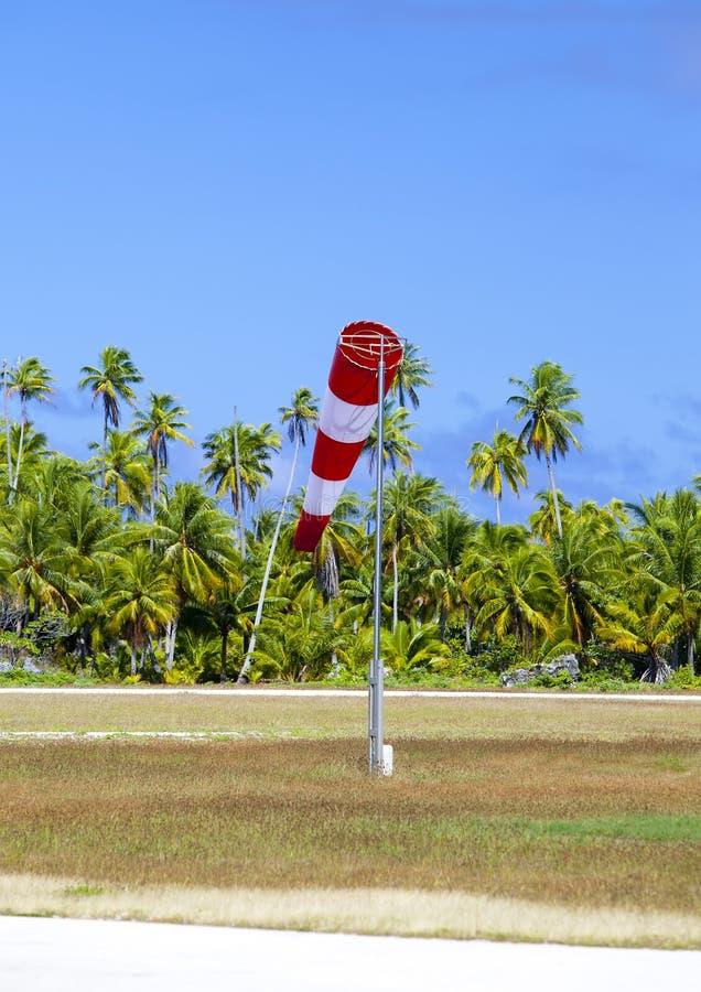 Szyszkowa wiatrowa miara wiatrowego kierunku w małym lotnisku na tropikalnej wyspie z drzewkami palmowymi przy pasem startowym fotografia stock