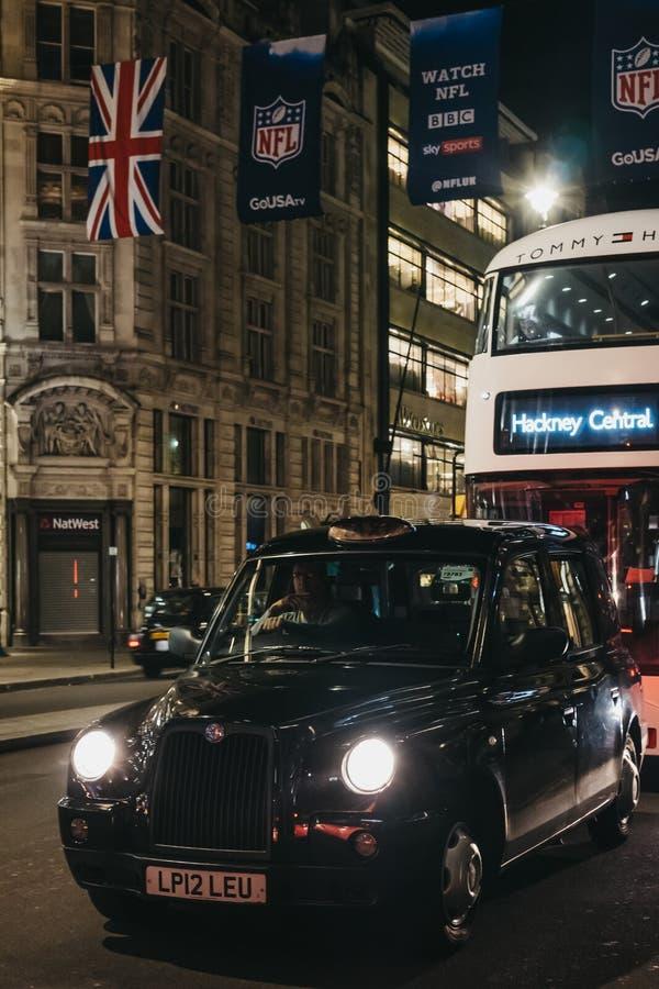 Táxi e ônibus pretos em Regent Street, Londres, sob bandeiras do NFL, na noite imagens de stock