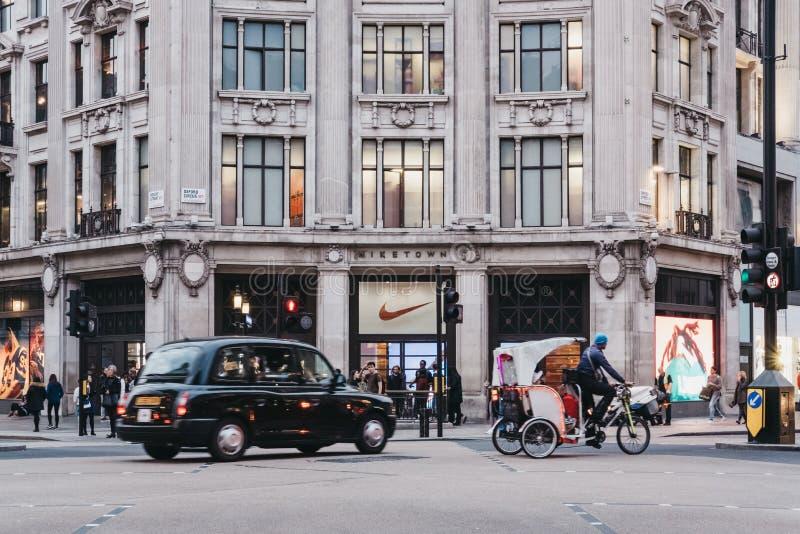 Táxi preto e riquexó que passam na frente de Nike Town, Londres, Reino Unido fotos de stock royalty free