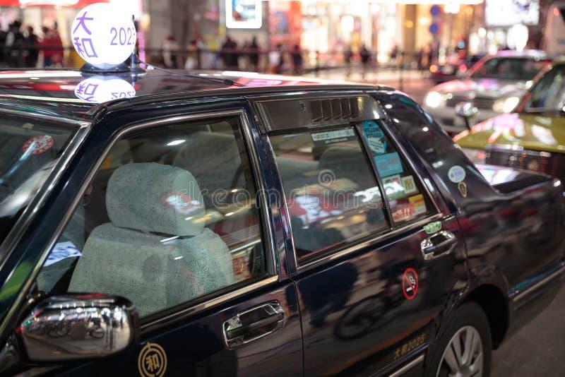 Táxi preto iluminado nas ruas do Tóquio fotografia de stock