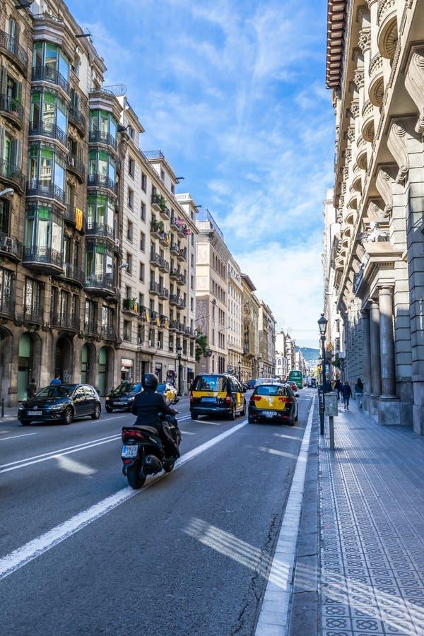 Táxis de táxi, carros privados e um motociclista em um dia ensolarado nas ruas de Barcelona e nos pedestres que andam na estrada fotos de stock royalty free