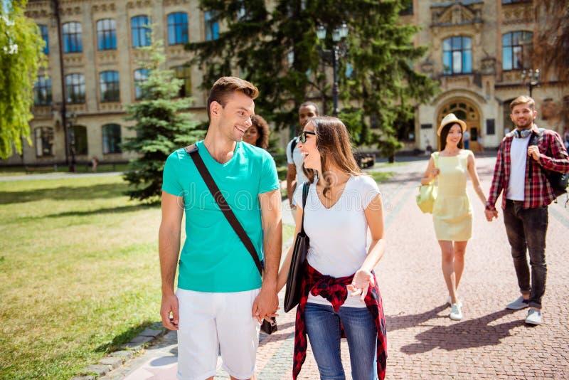 Tão bonito! Os pares de estudantes internacionais estão andando após s fotografia de stock