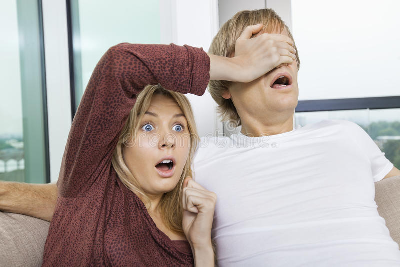 Täckande mans för chockad kvinna ögon, medan hålla ögonen på TV hemma royaltyfria bilder