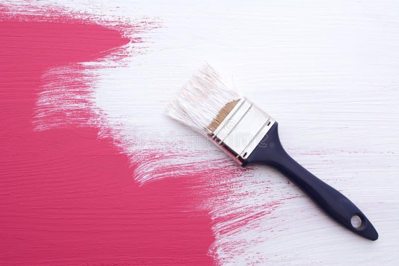 Täckande rosa färger målar med ett lag av vit emulsion arkivfoton