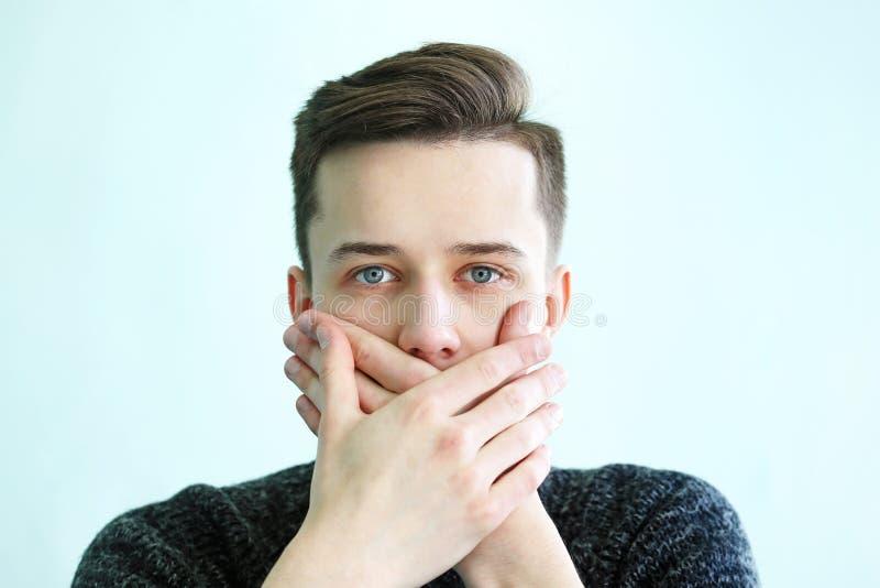 Täckt mun för ung man med händer royaltyfria bilder