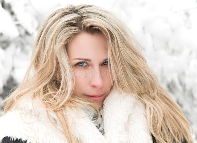 Täckte den blonda kvinnaståenden för härligt långt hår, vintern, snö trädbakgrund arkivbilder