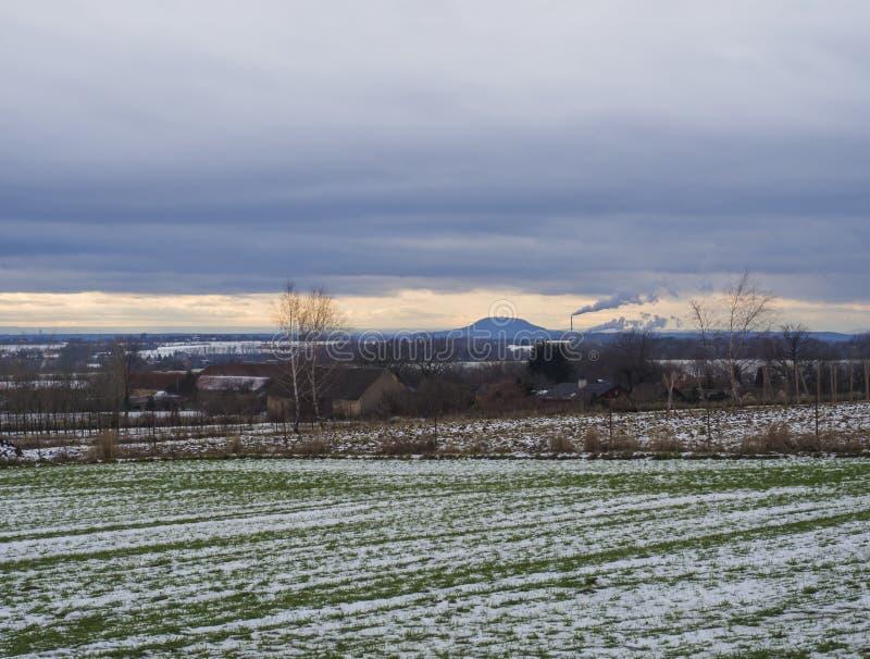 Täckte det lantliga landskapet för vintern med grön snö fält på solnedgången Sikt av bergrevakullen med att röka lampglaset royaltyfri fotografi