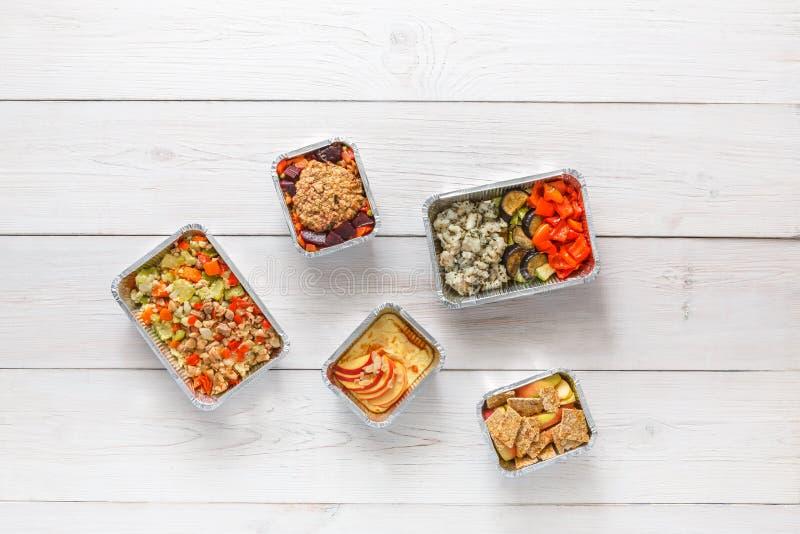 Tägliche Mahlzeitlieferung in der Draufsicht der Folienbehälter über weißes Holz lizenzfreie stockfotografie