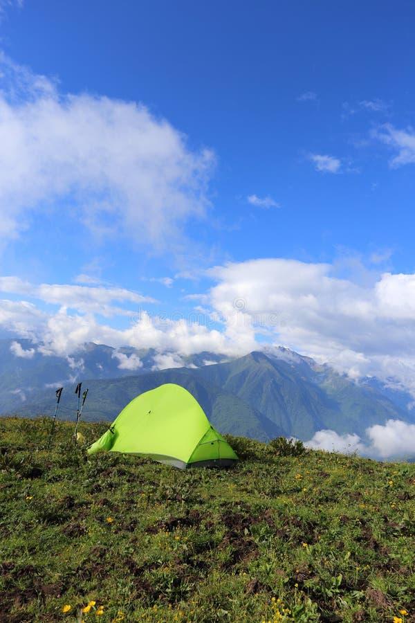 Tält för fotvandrare_ s på det höga berget, med snöberg i bakgrunden royaltyfri bild