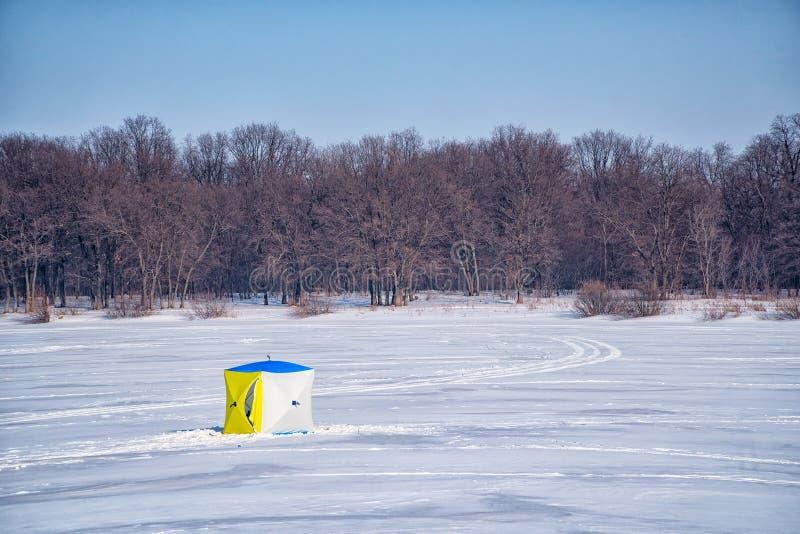 Tält för vinterfiske på en djupfryst sjö arkivfoto