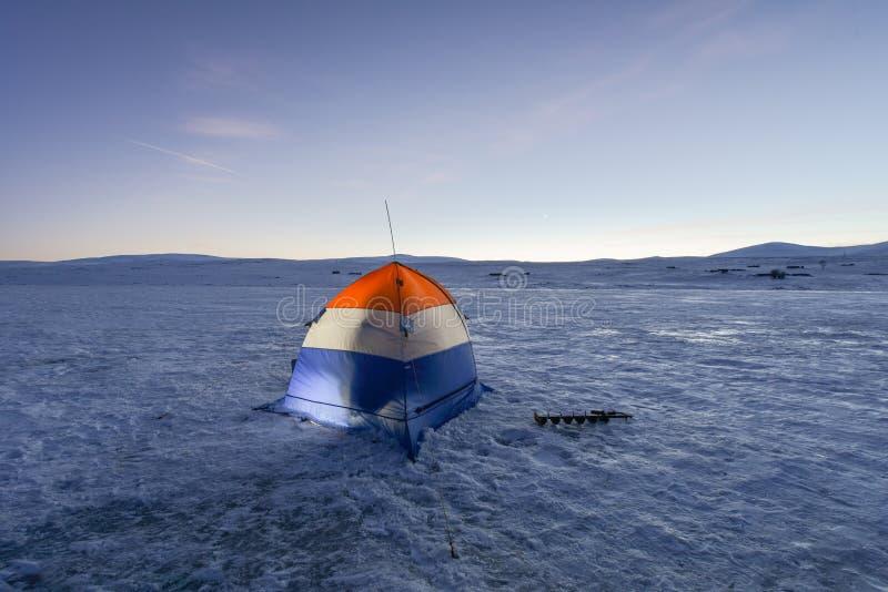 Tält för vinterfiske på en djupfryst sjö fotografering för bildbyråer