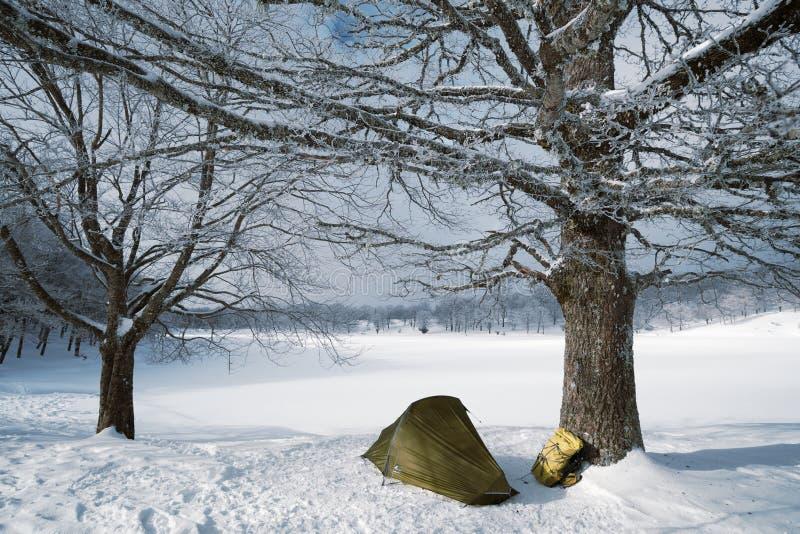 Tält och ryggsäck vid den djupfrysta sjön fotografering för bildbyråer