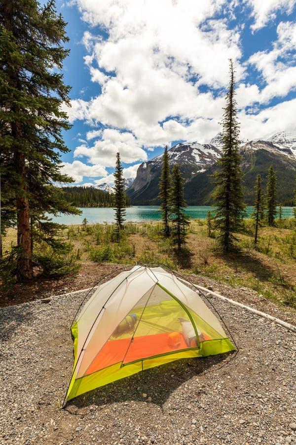 Tält på alpin sjöshoreline som omges av berg royaltyfri foto