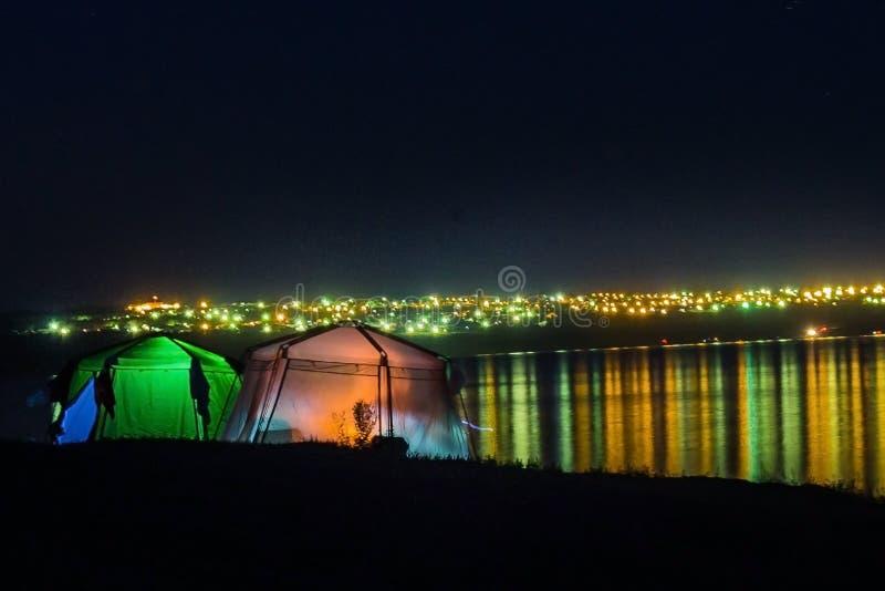 Tält på bakgrunden av vatten och ljus royaltyfri bild