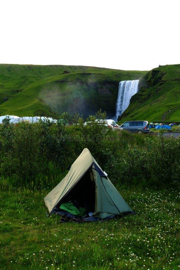Tält på den Skogar campingplatsen - Skogafoss i bakgrunden royaltyfri fotografi
