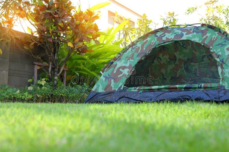 Tält som campar på gräsmattacampingplatsen för grönt gräs, utrustning för tur royaltyfria foton