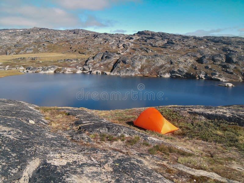 Tältet kastade upp vid sjön i det steniga området, Grönland arkivfoton