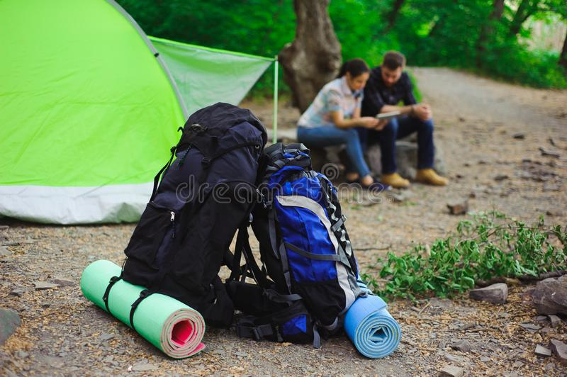 Tältet, två ryggsäckar nära ett turist- spår i berg royaltyfri fotografi