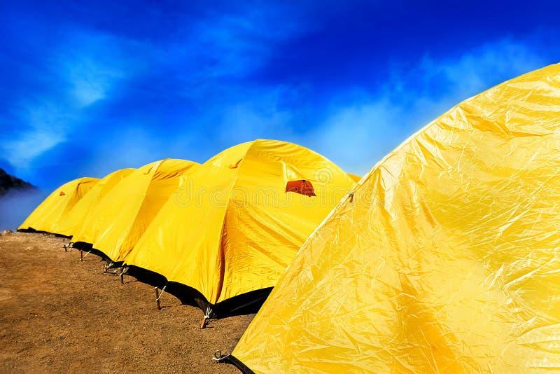 Tältplats i bergen Många gulnar tält mot den blåa himlen royaltyfria foton