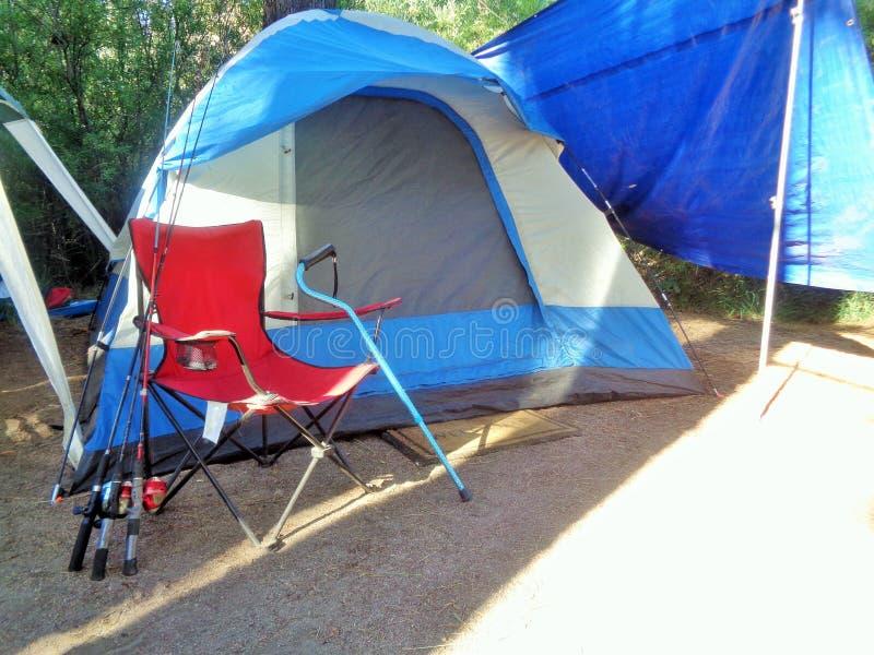Tältplatsplats med ett tält som går rottingen och fiska Poles som lutar mot en fällstol royaltyfri bild