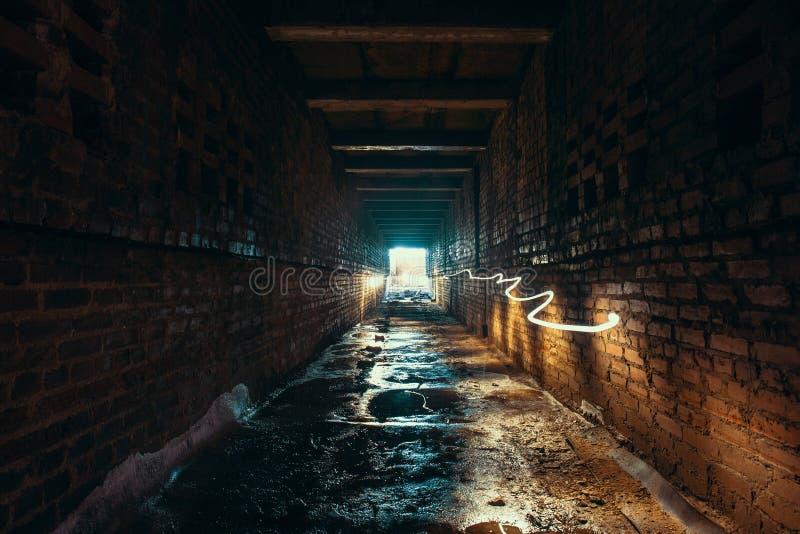 Tänd och gå ut i slut av den mörk lång tegelsten övergav industriella tunnelen eller korridoren eller förse med kloaker kanalen,  arkivfoton