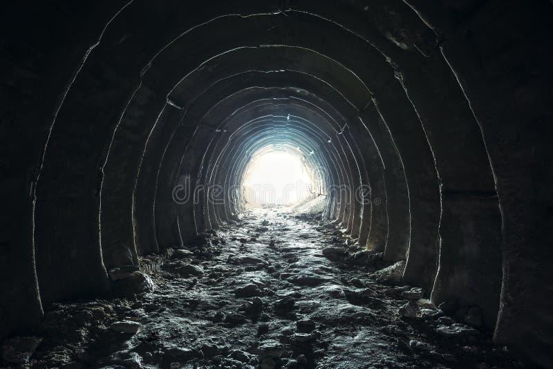 Tänd och gå ut slutligen av den mörka långa tunnelen eller korridoren, väg till frihetsbegreppet Industriell rund kritaminpassage royaltyfria bilder