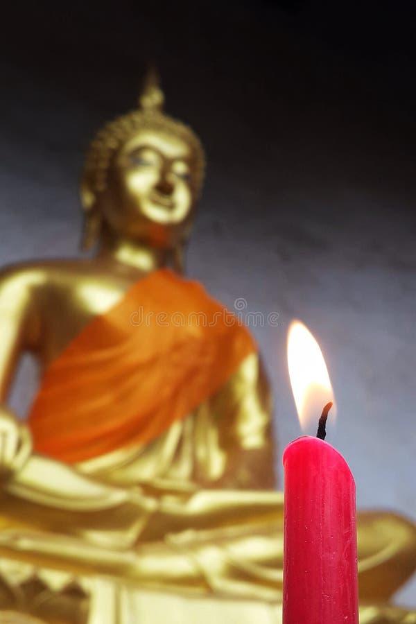 Tänd röd stearinljus med den buddha statyn arkivbild