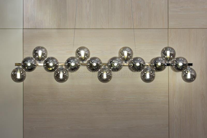 Tända bollar på ljuskronan i lampljuset, ljusa kulor som hänger från den långa stången, silverhängelampor på ljuset arkivfoto