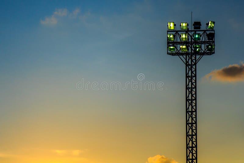 Tända eller strålkastaretorn av stadion på himmel och molnet på solnedgång- eller aftontid arkivbilder