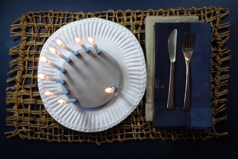Tända runda menoror på en vit platta semestrar matställebakgrund arkivfoton