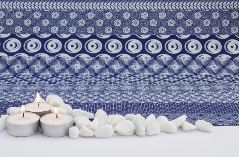 Tände liten vit tre stearinljus med vita kiselstenar och indigoblå prin royaltyfri bild