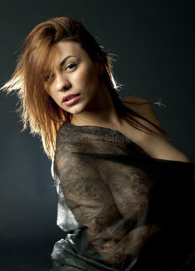 Tänder den blonda flickaståenden för det provokativa mörkret över svart bakgrundsbaksida royaltyfri fotografi