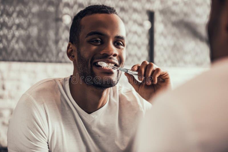 Tänder för Afro--amerikan manlokalvård i badrum arkivbilder