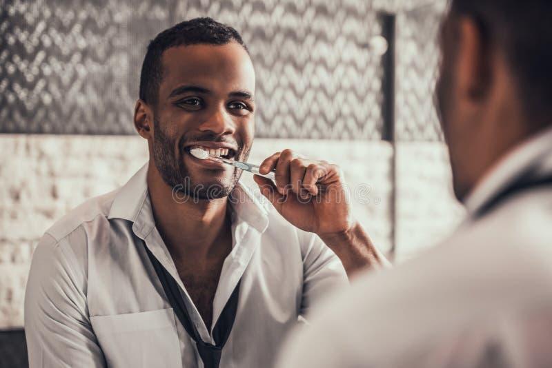 Tänder för Afro--amerikan manlokalvård i badrum arkivfoton