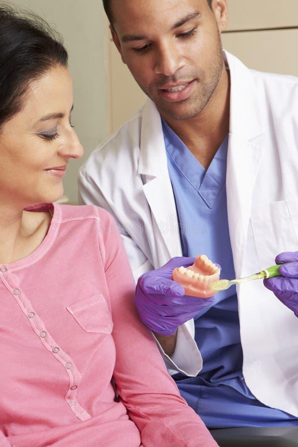 Tänder för tandläkareDemonstrating How To borste till den kvinnliga patienten arkivbilder