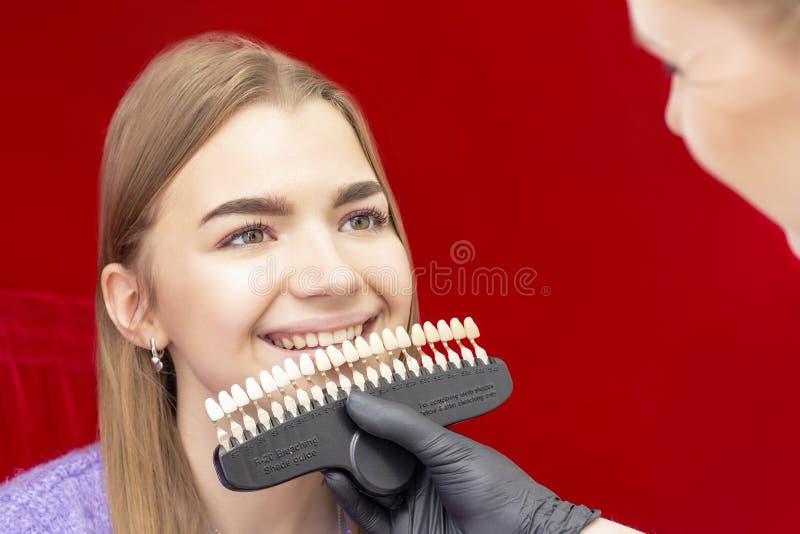 Tänder som gör vit tandläkaren för tillvägagångssättflickamottagandet för tänder som gör vit doktorn, väljer upp färgen av tänder royaltyfri bild