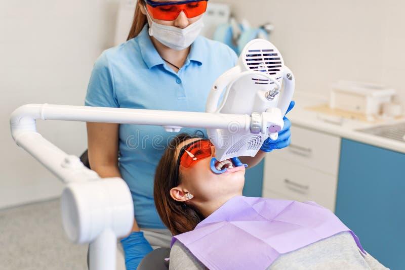 Tänder som gör vit tillvägagångssättet för nätt lycklig kvinnlig patient i en tand- klinik fotografering för bildbyråer