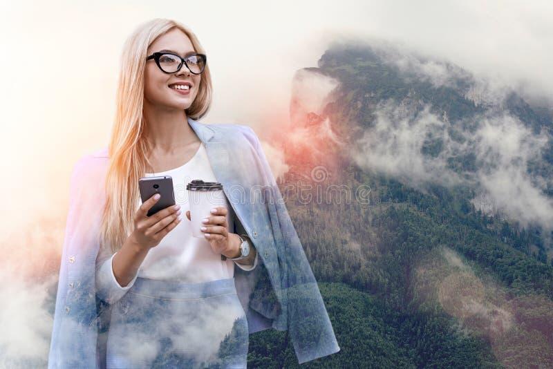 tänka för affär Gladlynt kvinna i klassisk blå dräktinnehavsmartphone och kopp kaffe, medan stå royaltyfri foto