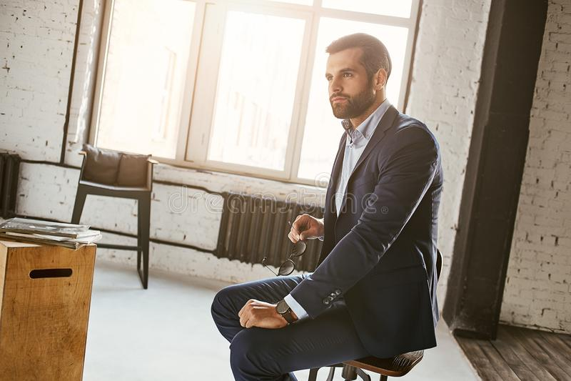 tänka för affär Stående av den attraktiva affärsmannen som bär stilfullt dräktsammanträde i fåtölj och bort ser arkivfoton