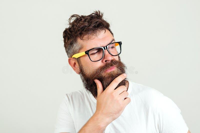 Tänka för Hipsterman som trycker på hans skägg Uppsökt grabb i exponeringsglas som är fundersamma, på vit bakgrund Stilig skäggig royaltyfri fotografi