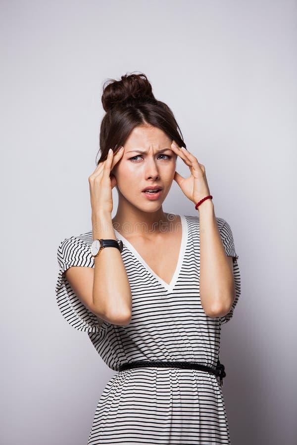 Tänka, tröttat eller dåligt med den unga kvinnan för huvudvärk som isoleras över vit bakgrund royaltyfria foton