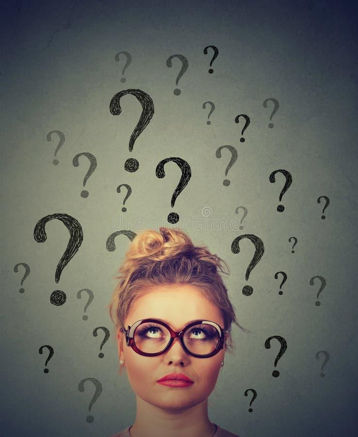 Tänkande affärskvinna med exponeringsglas som ser upp på många frågefläckar ovanför huvudet arkivbilder