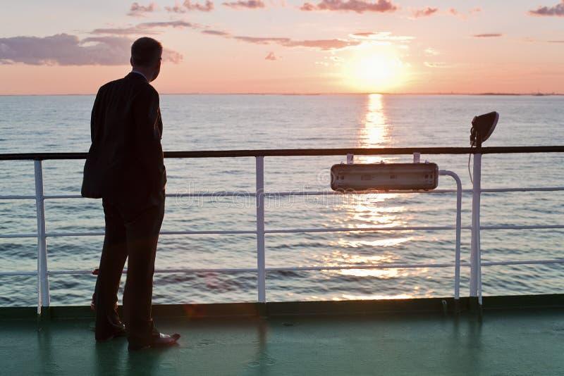 Tänkande affärsman och röd solnedgång på en färja arkivfoto