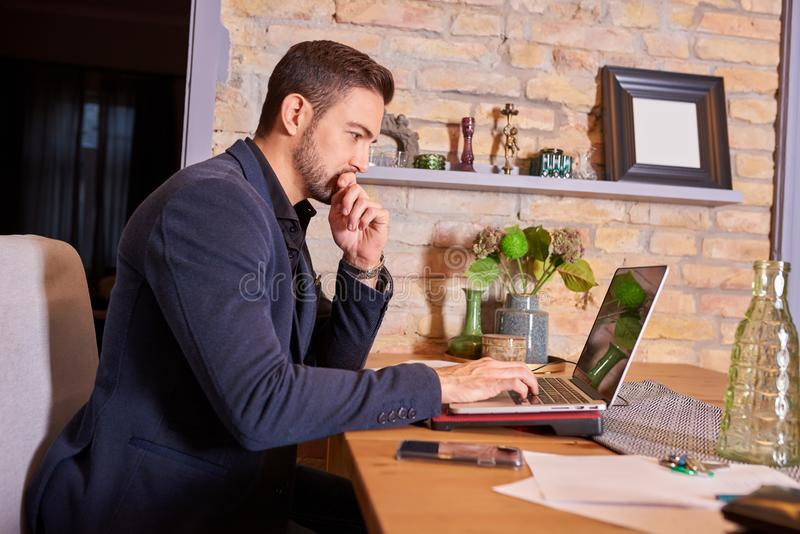 Tänkande affärsman som använder bärbara datorn royaltyfria bilder