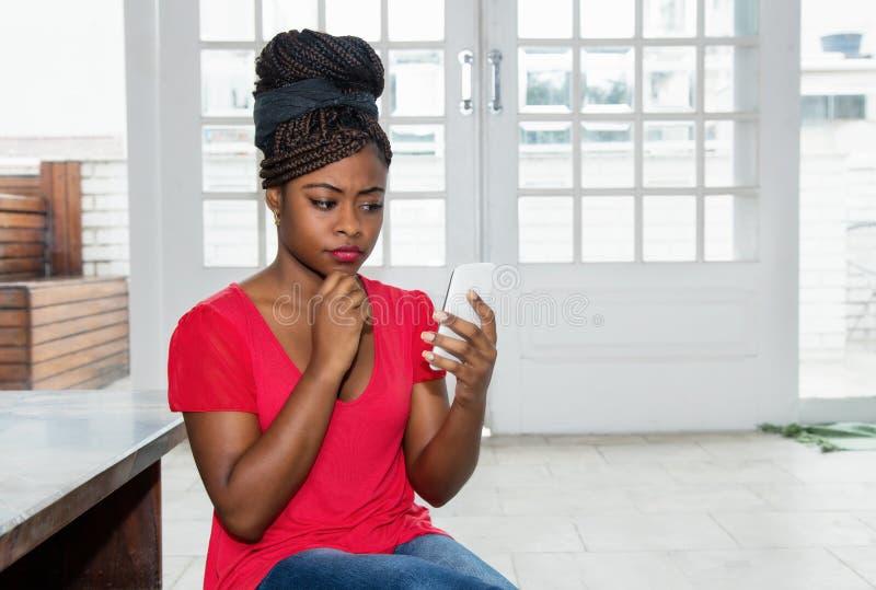 Tänkande afrikansk amerikankvinna med mobiltelefonen arkivbild