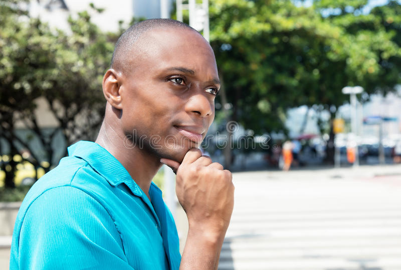 Tänkande afrikansk amerikanman i ljus skjorta royaltyfri fotografi