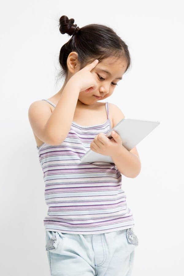 Tänkande asiatiskt barn med minnestavladatoren fotografering för bildbyråer