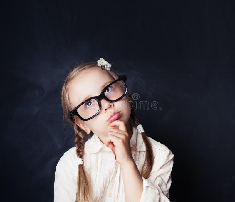 Tänkande barn Liten flicka i exponeringsglas på den svart tavlan royaltyfri fotografi